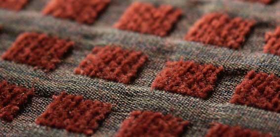 tecido composto por fios coloridos e quadrados de tecido felpudo vermelho enfileirados simetricamente na vertical e horizontal
