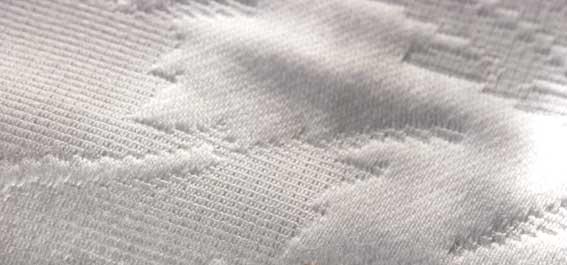 tecido branco com desenhos bordados com linha branca