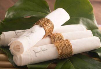 4 guardanapos em argolas de capim dourado sobre folha de costela de adão