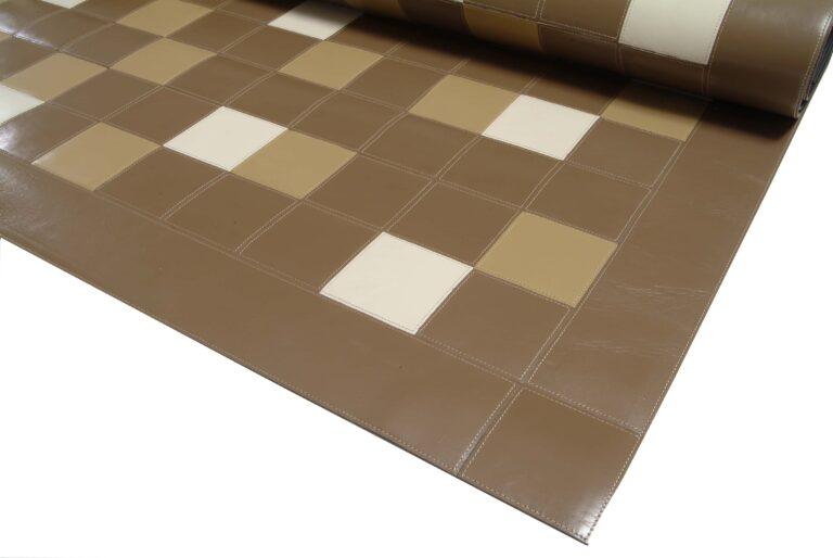 tapete de couro marrom, uma parte enrolada e outra esticada, a parte não enrolada mostra o desenho feito pela costura semelhante a uma grade quadrículada, com alguns quadrados aleatoriamente preenchidos pelas cores branca, bege e marrom
