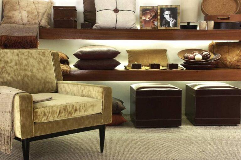 2 prateleiras baixas de madeira com almofadas, quadros e enfeites nos tons de marrom e amarelo terroso, abaixo puffs de couro marrom e a frente, poltrona amarela de veludo sobre carpete marrom claro