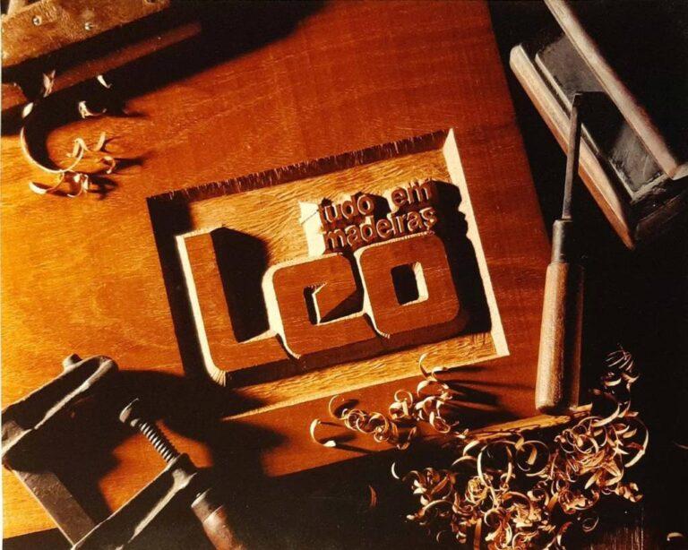 """uma madeira com a frase """"tudo em madeiras Leo""""gravada, ainda com lascas de madeira devido o trabalho da escrita e ferramentas recém utilizadas"""