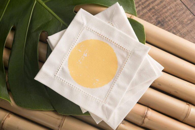 5 porta copos brancos de tecido de algodão e estampa de sol, empilhados desordenadamente sobre folhas de costela de Adão e caules de cana