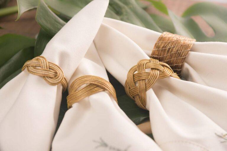 4 guardanapos de tecido branco em argolas de capim dourado trançadas de diferentes modos, sobre folha de costela de adão