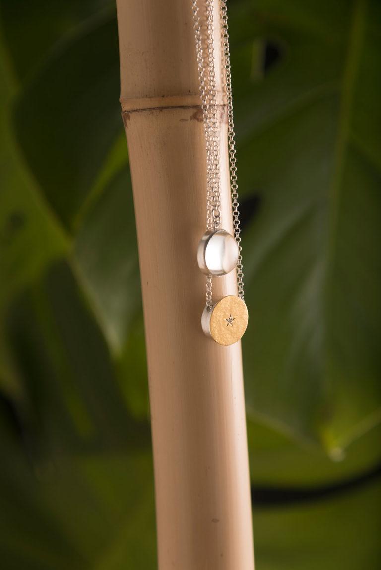 escapulário com um pingente dourado e outro transparente, corrente prata, pendurado em bambu com folhas verdes desfocadas no fundo