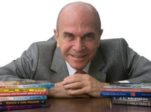 retrato profissional de homem de terceira idade, vestido com terno cinza e gravata, com alguns livros à sua frente