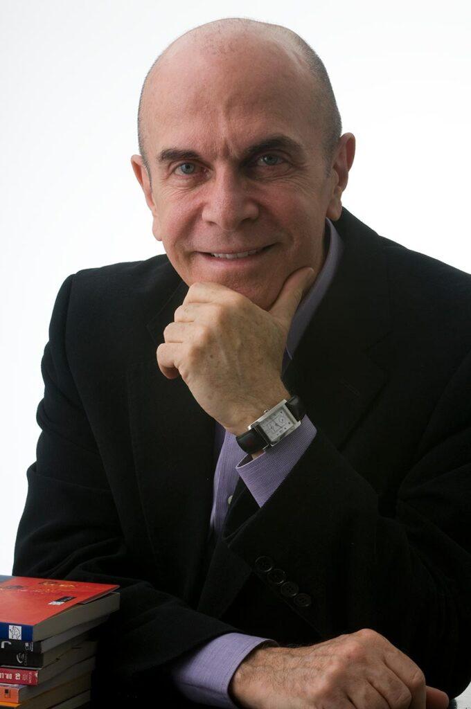 retrato profissional de homem de terceira idade,vestido com terno preto e camisa violeta, com mão sob o queixo, alguns livros na sua lateral