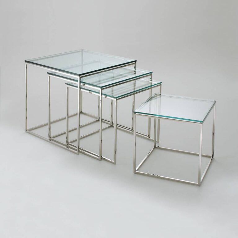 conjunto de 4 mesinhas, com estrutura semelhante a cubos e tampo de vidro, organizadas uma dentro da outra da maior para menor como se formassem degraus