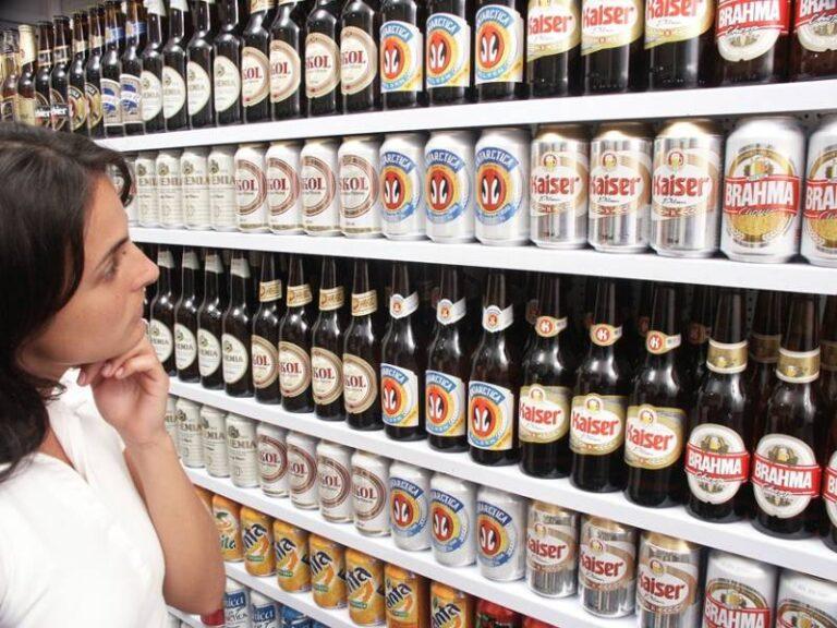 uma cliente observando prateleiras de supermercado com cervejas em latas e garrafas e alguns refrigerantes em latas expostos
