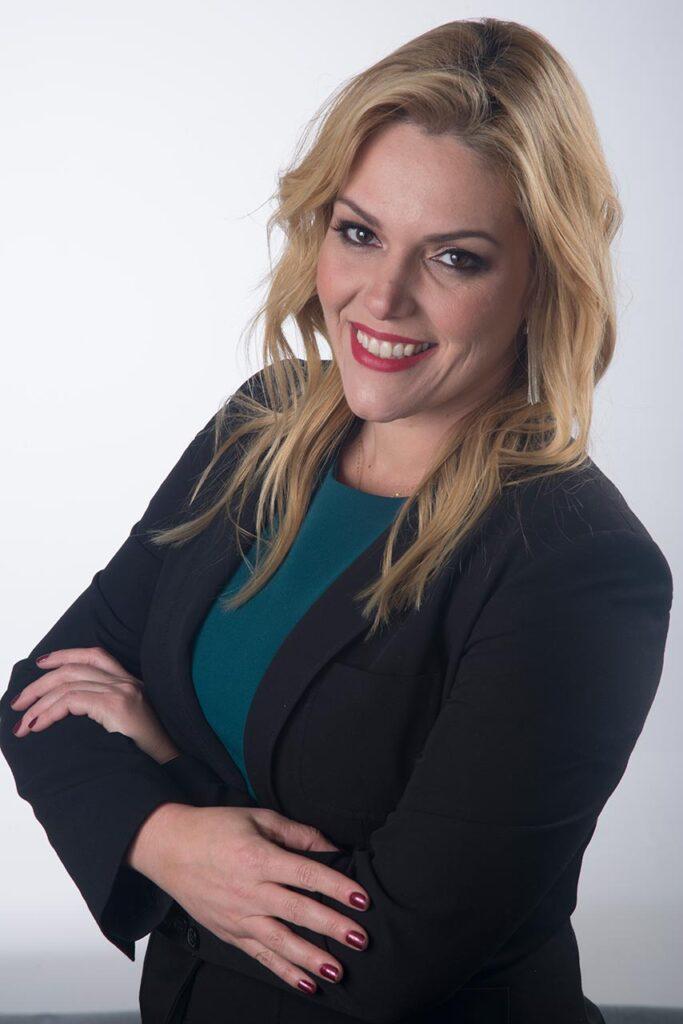 retrato profissional de mulher loira, jovem, sorrindo, vestindo blazer preto e blusinha verde escuro, braços cruzados, ambiente claro